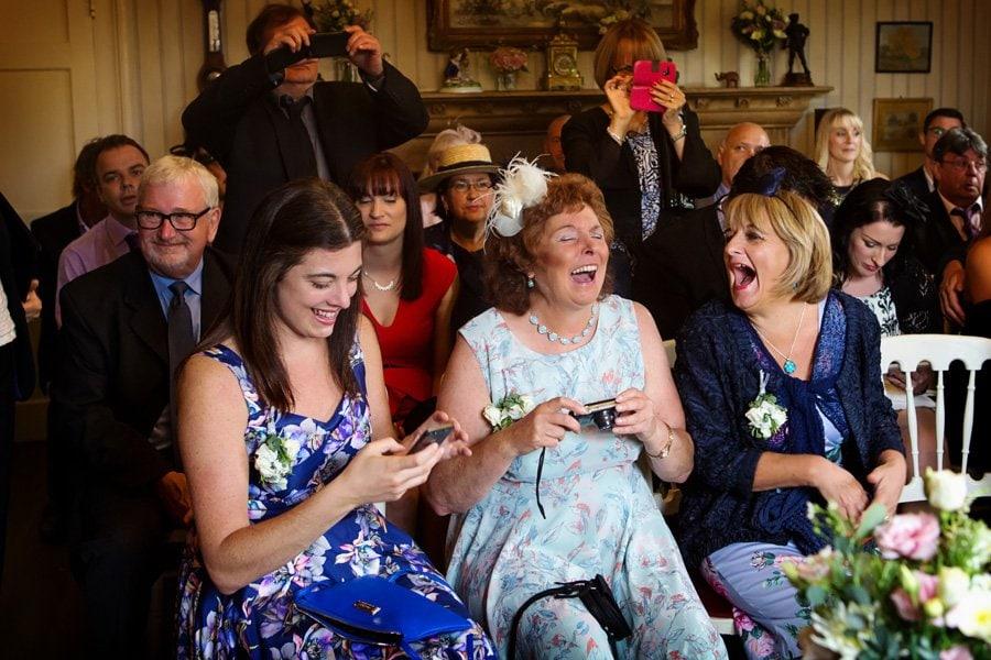 wedding guests laughing at Hambleton Hall Nottingham wedding photographer