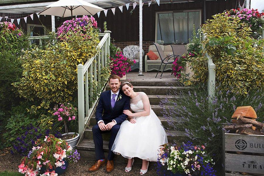 bride and groom sitting on steps at floral media