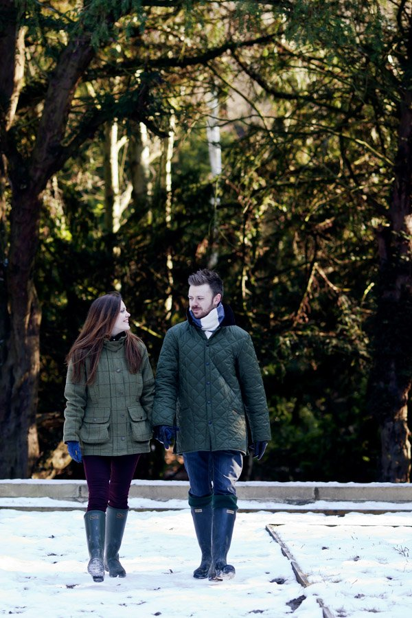engaged couple walking in snow at elvaston castle