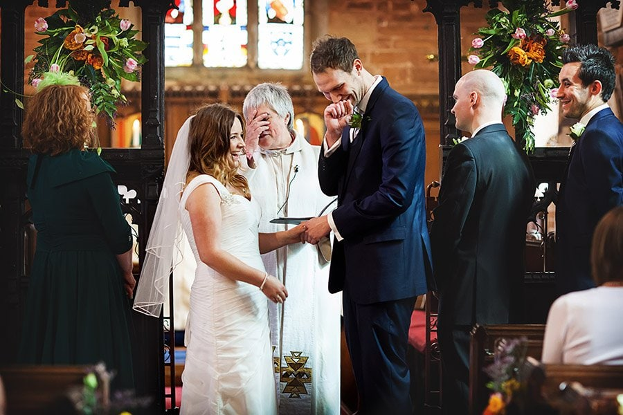 vicar laughing with bride and groom in Nottingham church