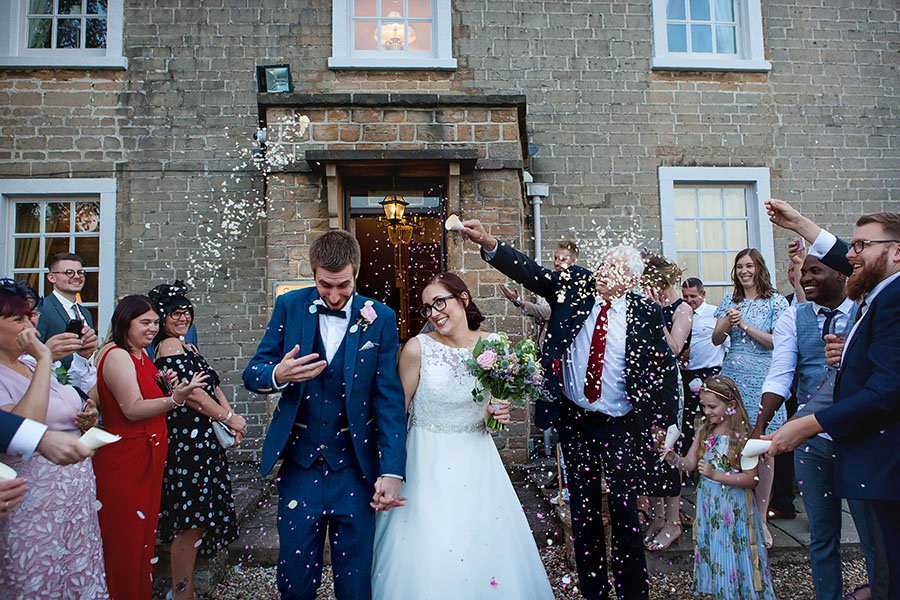 guests throwing confetti on bride and groom natural wedding photography