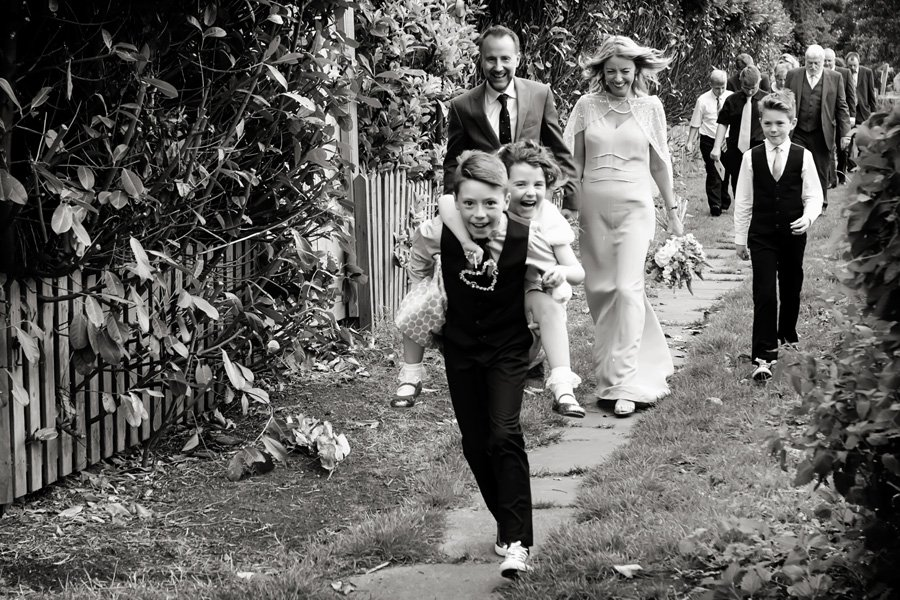 Nottingham wedding photographer with wedding guests walking from church and children on piggy back