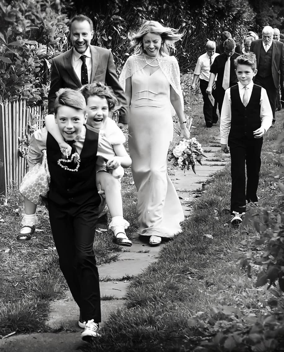 wedding guests laughing walking from nottinghamshire church uk wedding photographer