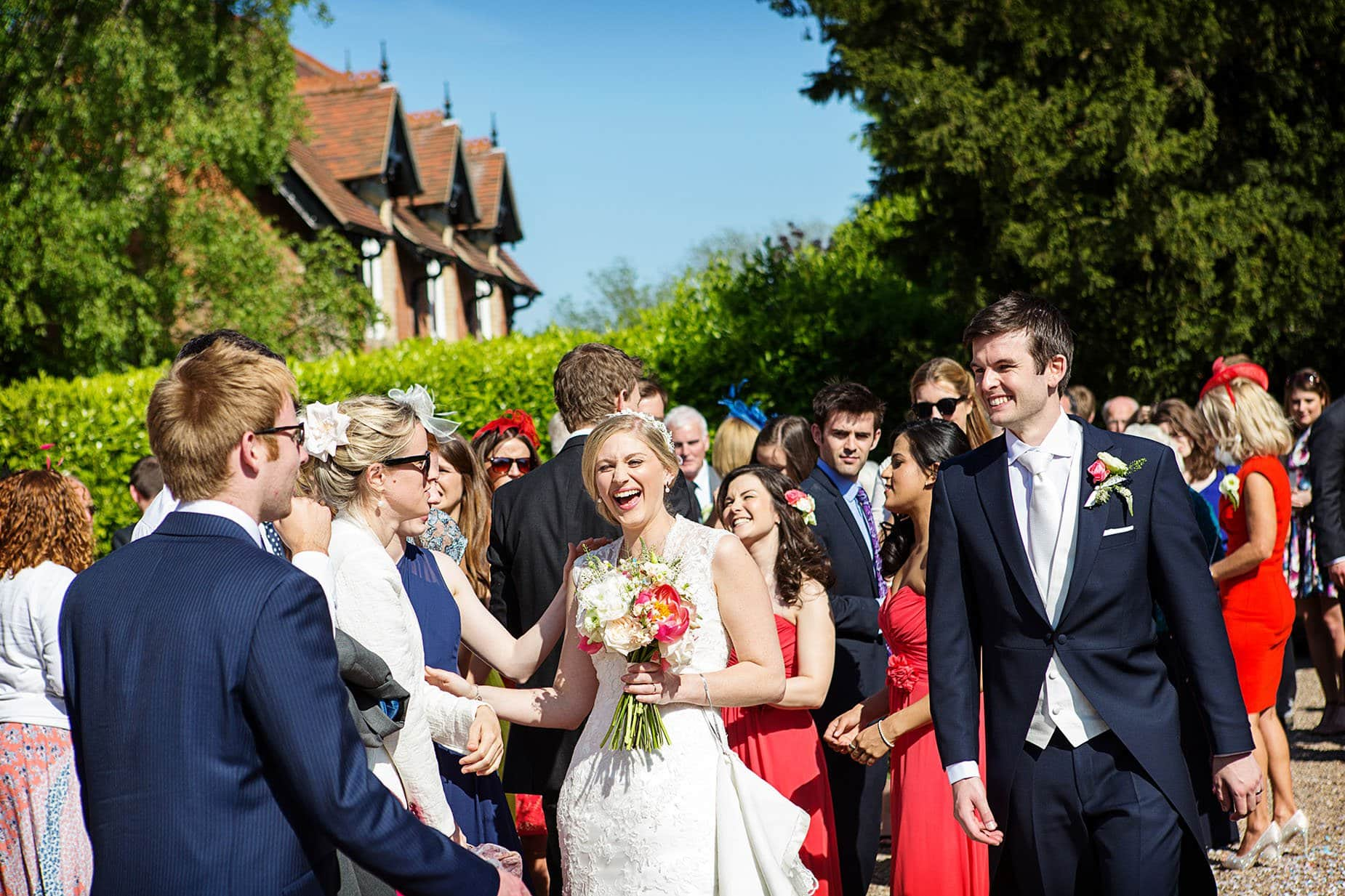 uk wedding photographer wedding guests outside church laughing