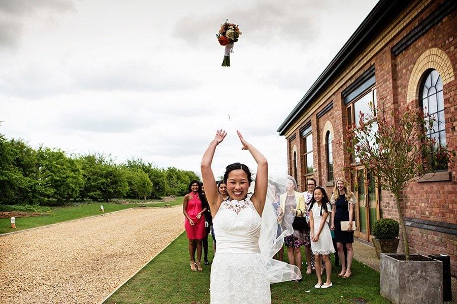 bride throwing bouquet uk wedding photography