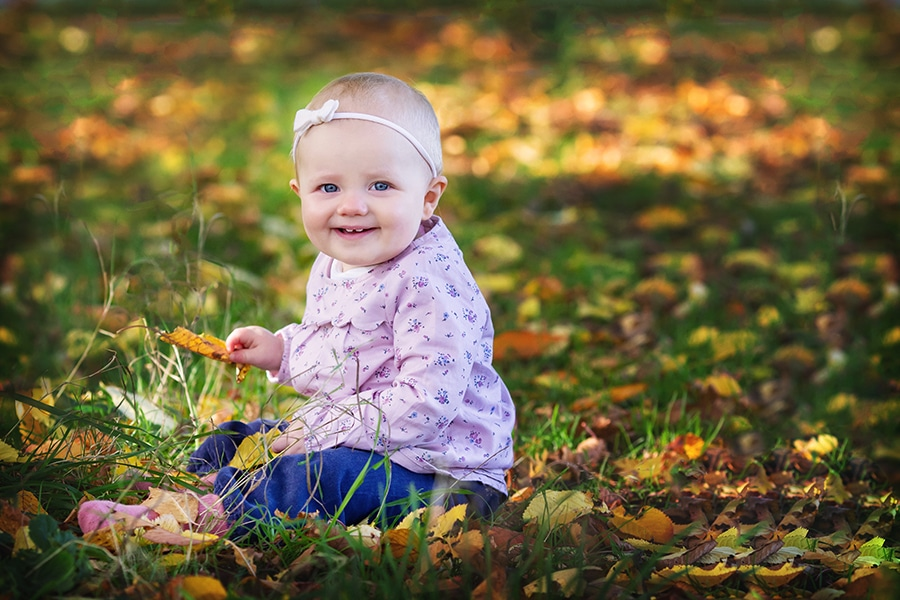 baby girl sititng in autumn leaves