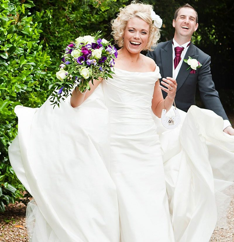 bride and groom laughing with wind blown dress