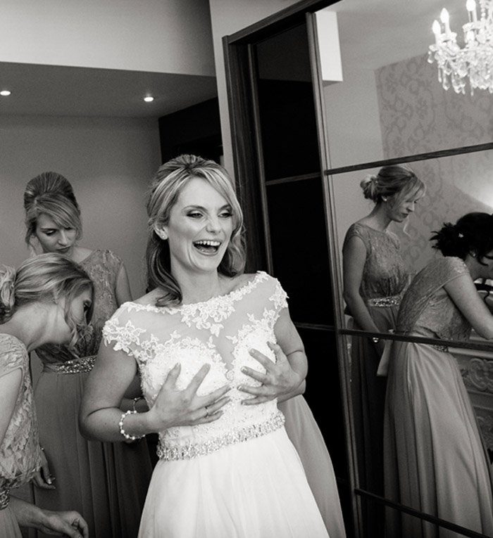 bride laughing being fastened into dress