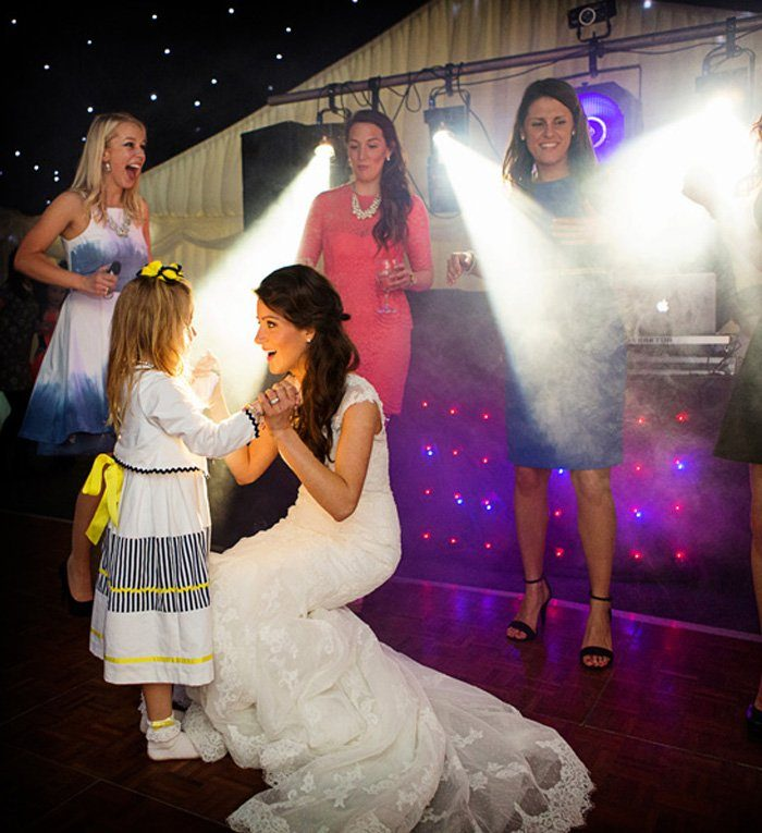 bride dancing with young girl at wedding
